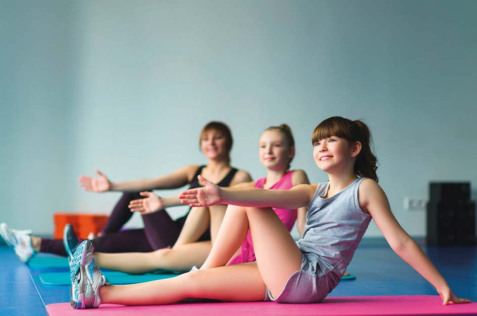 children yoga stretching on gym mats