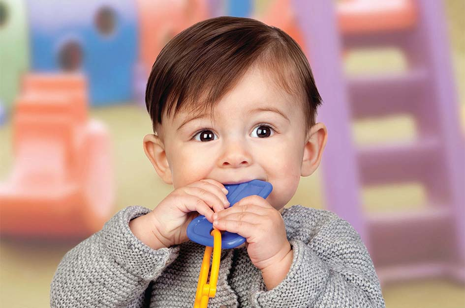 Male toddler eating plastic keys