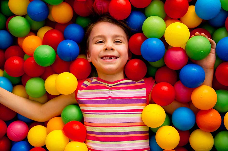 child laying in a ball pit smiling