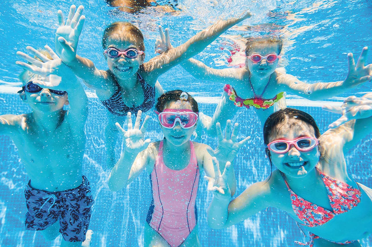a group of children smiling in a swimming pool underwater