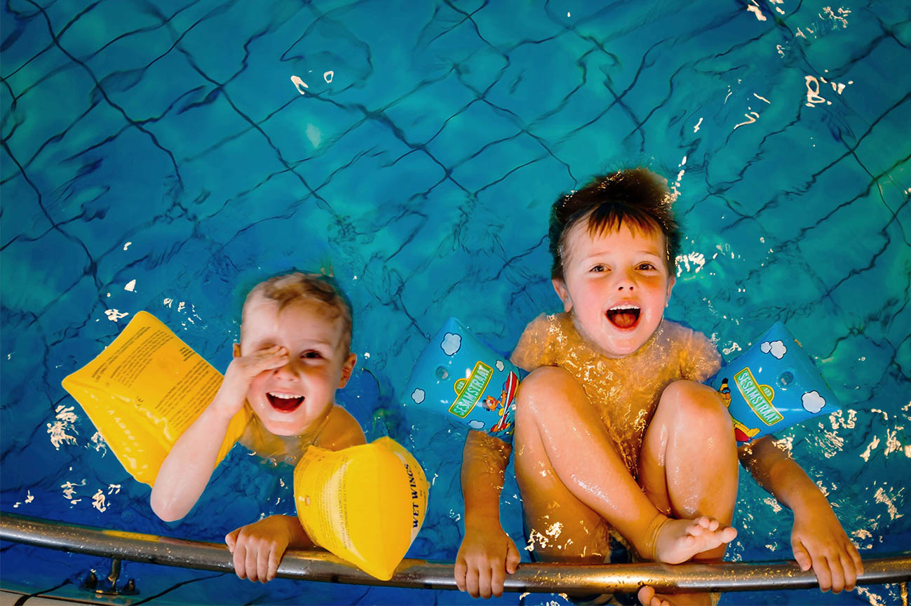 two young boys in a swimming pool laughing with arm bands