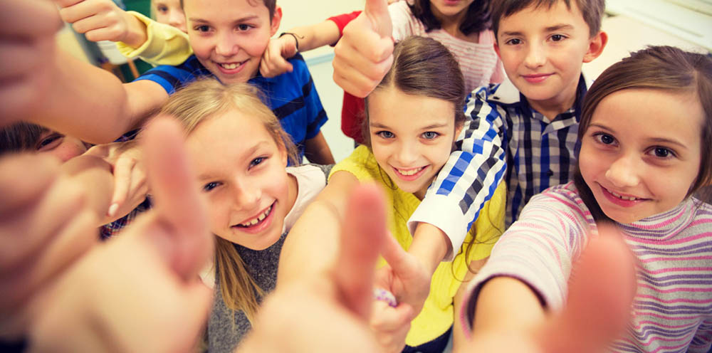 Group of kids giving thumbs up