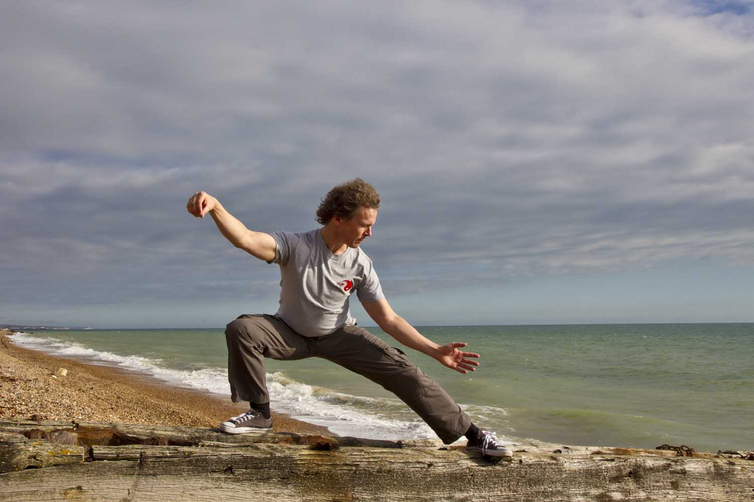 man doing qigong at the beach