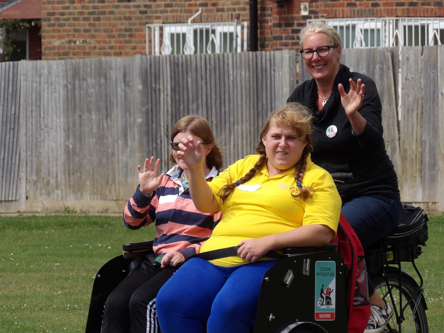 three people waving, two in wheelchairs