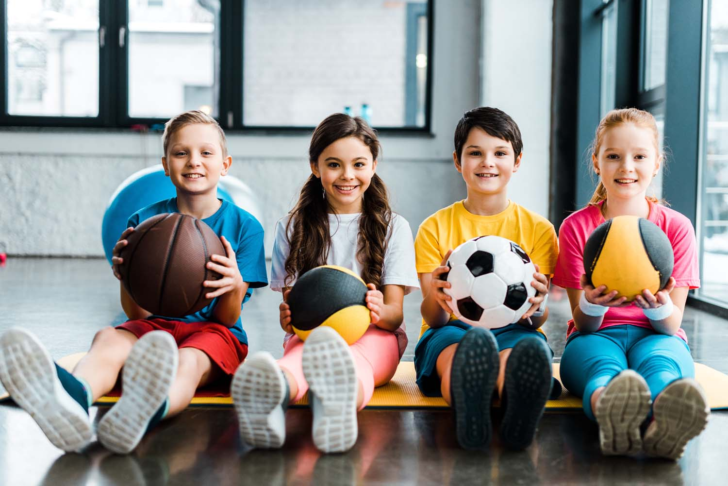 kids sitting on a fitness mat with sports balls