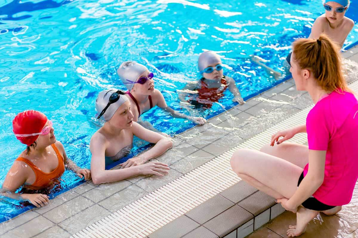 kids in a swimming lesson with a teacher
