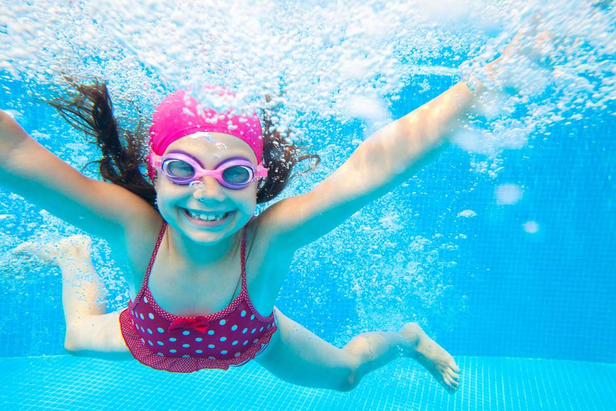 girl in a pink hat smiling underwater