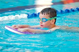 a boy swimming with a floatation device