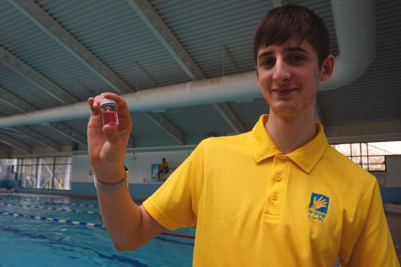 a young man in a lifeguard uniform next to a pool holding a small container of water